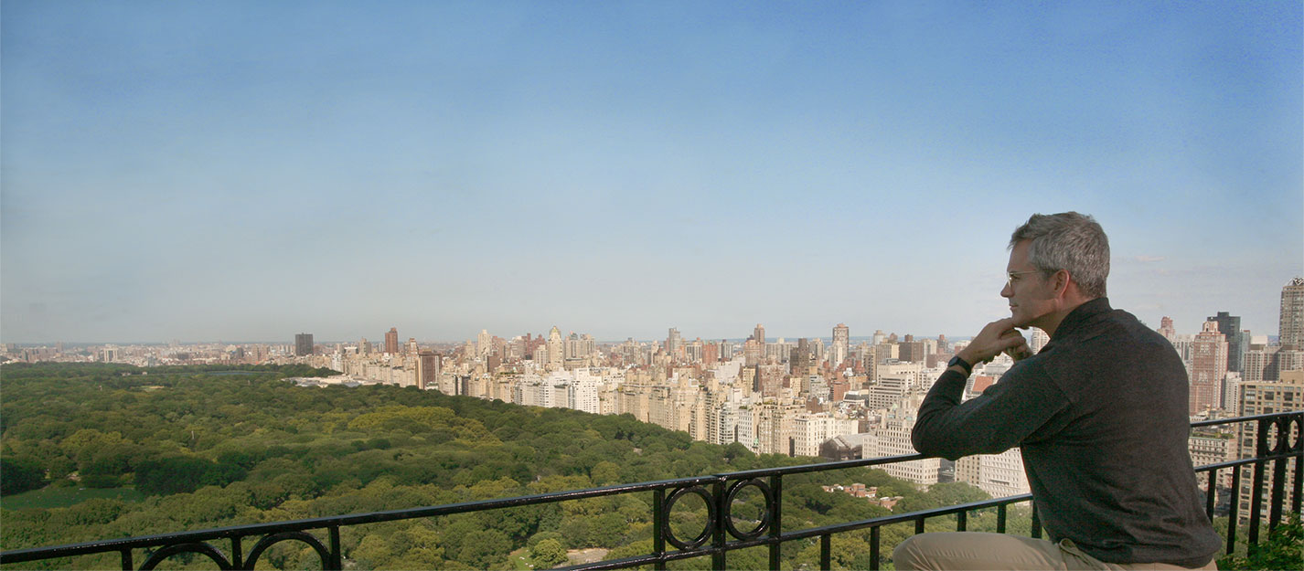 Man overlooking central park from his Hampshire House balcony.